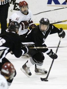Mandan's Grant Aasand, middle, looks to pass the puck against Bismarck on Tuesday. (Mike McCleary/Bismarck Tribune)