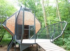 A diamond-shaped woodland cabin on legs