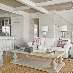 Galveston Bay, Texas, living room with shiplap walls, mercury glass lamps with turquoise finials, coral-patterned throw pillows, and a sea grass rug. - coffee table idea?