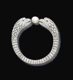 AN EXQUISITE ART DECO NATURAL PEARL, DIAMOND AND EMERALD BANGLE, PROBABLY BY LACLOCHE FRÈRES