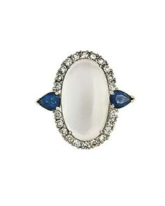 An 18ct white gold moonstone, sapphire and diamond ring  The oval cabochon moonstone in a brilliant-cut diamond surround to pear-shaped sapphire shoulders, hallmarked London