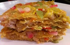 layers of tostadas with navy beans, garlic, cream cheese, red onion, cumin and extra sharp cheddar in a green chile sauce.