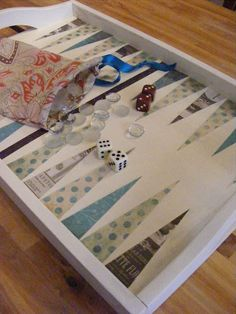Make a Pretty Backgammon Board ~ Paint a thrift store tray, cut pieces of fabric or scrapbook paper into triangles and glue with Mod Podge, cover with several coats of polyurethane. Add glass pieces or buttons, dice and a fabric bag to store them in.