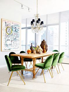 Nate Berkus-designed dining room with rustic wooden dining table, green velvet and brass chairs, crystal chandelier with black lampshades.