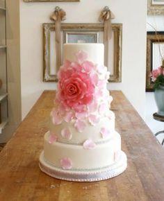 O bolo simples de casamento está invadindo a cena nas festas de casamento. Os bolos tradicionais, cheios de detalhes e poluídos, muitas vezes acabam não valorizando nenhum detalhe. Isso porque cada detalhe concorre entre si. Veja nesta foto como um único detalhe (uma flor rosa) salta aos olhos e acaba por valorizar o bolo como um todo. Este detalhe não concorre com nenhum outro. Este bolo de casamento simples acaba chamando mais a atenção do que um bolo clássico de noiva.