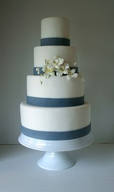 4 tier fondant wedding cake with blue fondant ribbon and handmade sugar flowers