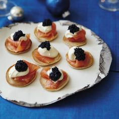 Caviar and smoked salmon on mini Blini with cream
