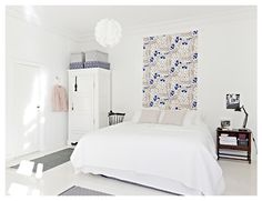 White Scandinavian bedroom-like the material hanging on the wall behind the bed, great deco idea