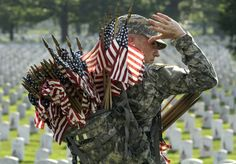 Army Spc. Justin Immerso places flags in front of head stones at Arlington National Cemetery in preparation for Memorial Day