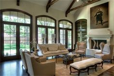 Great Room - Cathedral ceiling with stained wood beams, fireplace with carved stone surround hearth and mantel, old world built-in stained cabinetry with brass wire insert, open to kitchen and breakfast with wall of transom French doors to back yard