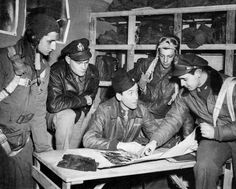 Major Jimmy Stewart talks over the final details of a mission with flyers about to take off. England, April 19, 1944.