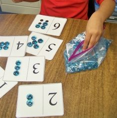 Kindergarten Math Centers  Would also have the cards colour coded, perhaps with a pattern to put the counters on.   If children need fine motor advancing, I'd have textile resources to put on with tweezers.