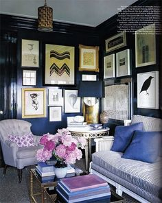 great gallery wall, cozy dark blue walls and nice mixing of styles.  I'd love two little chairs like those!