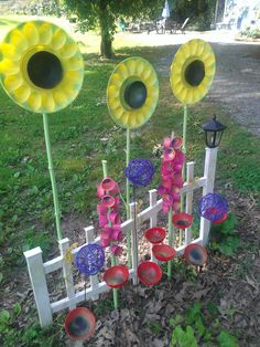 Made for my cottage driveway where nothing will grow!  Sunflowers: plastic deviled egg plates and bowls glued to bamboo stalks. Hollyhocks: 2 oz cups glued to bamboo stalks. Purple allium: grapevine balls glued to wire plant supports. Poppies: plastic bowls glued to wire plant supports.  Paint creatively, and voila!  Instant folk art garden!  Also great for Day Care and Kindergarten  ~Jo White, Blairsvillager.com garden