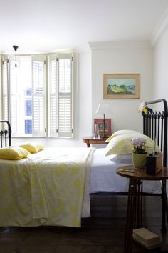 Bedroom with yellow accents and white interior shutters, Remodelista