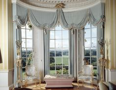 The Drawing Room at Hinton Ampner, Hampshire, England with views from the windows and heavily draped curtains. After the fire of 1960 the room was redesigned to complement the 18th century styles of the other rooms