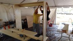 """How to Build a Side-Fold Murphy Bunk Bed: Once the pivot point is established, pocket-screw the concealed outside edges of the frame sides and top together. Use spare strips of plywood across the back top and bottom to help keep the frame square. Cut four approximately 4"""" x 80"""" pieces of plywood and laminate both sides of the outer face of the vertical frame legs with 1.25"""" wood screws. Transfer the pivot points and drill the vertical frame legs with a 5/8"""" bit. Epoxy the coupling nut in this h…"""