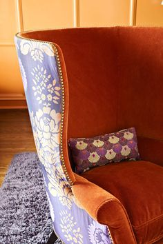 Orange wing back chair with contrasting outside back floral pattern.
