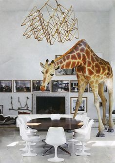 giraffe dining room - best modern whimsy with giant giraffe sculpture, concrete floors, terrazzo fireplace, brass chandelier and tulip chairs