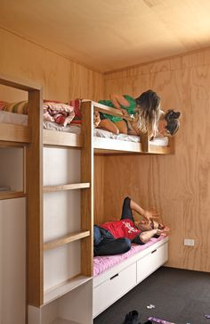 In a compact New Zealand beach house, space-saving bunk beds offer a fun place for the kids to retire in the evening. Photo by Simon Devitt.