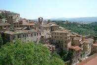 Perugia  -- home to two universities, a chocolate-kisses company,  a world-famous jazz festival in the summer -- is a walled city on a hilltop and a good central square. Its history goes back to the ninth century BC. Perugia is in the center of Italy and is the capital of the region of Umbria.