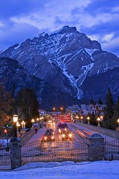 Banff Avenue is lit up at dusk with Cascade Mountain towering above the street in the background. Dusk in the winter is one of the most magical times of day, as can be seen here in this picture taken in Banff, Alberta, Canada.