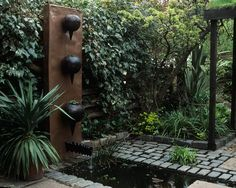 Water feature as sculpture! The points on these wall planters reflect the shape of water droplets as they fall. Love the metal backdrop. Design by Cleve West Landscape Design.