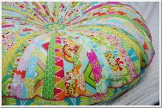 Floor pillow or pouf made from a jellyroll of fabric and stuffed like a beanbag!