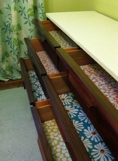 Line dorm room dresser drawers with gift wrap.