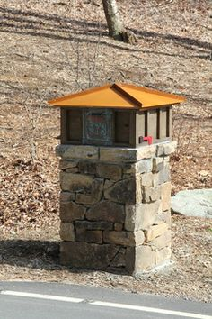 Mixed-material mailbox. Stone pillar, paneled-wood surround, metal pyramidal top. This concept is gorgeous. I imagine brick and a solid-color mailbox.