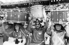 Members of the University of Nebraska-Lincoln Alumni Band, from left, Bob Jenkins of Omaha, Terry Tegtmeier of Omaha and Dennis Dodge of Hebron, Nebraska, find extra protection from the rain under their drums on Oct. 3, 1981. The Huskers defeated Auburn 17-3 in the 115th sellout game in Memorial Stadium. THE WORLD-HERALD