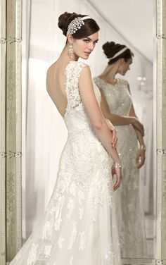 Sheath wedding gown features a vintage-inspired lace overdress with cap sleeves from Essense of Australia (Style D1549)