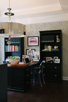 amazing spotted wall paper + black desk + bookcases + glam pendant light + Hermes trey + ghost chair