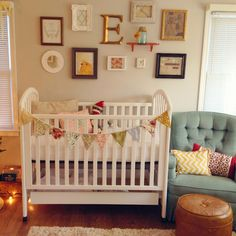 Nuetral baby room with pops of color from wall decor, chair, and pillows.