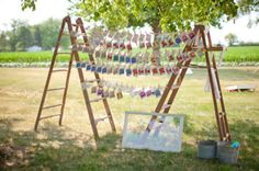flower seed packet escort cards strung between two rustic ladders | photo by http://www.kristinlavoiephotography.com