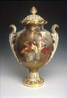 Vase and cover. 2002.C.434. 1865. Bone china. H : 49cm.  Vase and cover with acanthus finial in the rococo style after a Sevres shape, painted by Ludwig (Louis) Jahn.  The painted scene derives from a Watteau painting, with a scene of Harlequin and revellers, musicians and dancers.  There are also scrolled and gilded handles and foot. (the Minton archive is under threat) see www.artfund.org/...