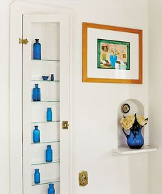 A display case made by retrofitting a built-in ironing-board cubby with a glass door panel and shelves   Photo: David Penton