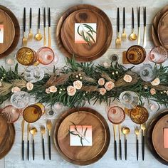 Natural, feminine table setting with blush colored flowers, greenery, wooden plates and brass utensils.