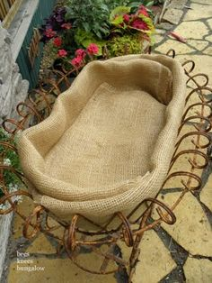 DIY:  Creative way to plant in a metal basket - fold a couple of layers of burlap, add potting soil & flowers. 5/13/11 post.