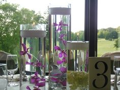 Lovely 3 tier vases with floating orchids. Check out the hand-painted wood table numbers.