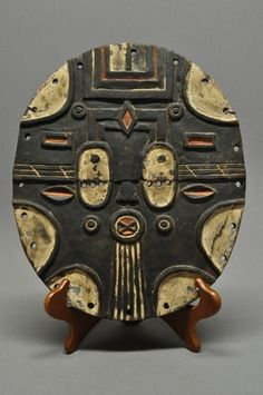 """This carved wood Teke mask from the Democratic Republic of Congo has white and red pigment. These masks were worn during weddings, funerals, as well as other events. This is a flat surface mask that is decorated with designs and symbols. The overall height is 14""""."""