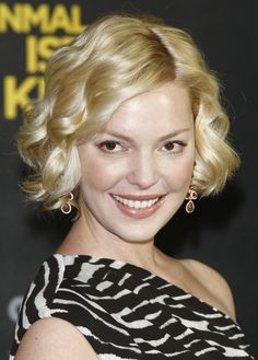 Katherine Heigl - Short Blonde Curly Bob Hairstyle - Katherine's thick hair is parted slightly off center and her shiny blond locks are curled into evenly sized spiral curls. By holding and pulling the curling iron vertically while rolling up and releasing the curl, Katherine's stylist has avoided the dreaded fishhook curl.