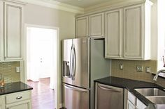 Refinished builder's grade cabinetry, new appliances, backsplash, lighting, countertops...everything including the kitchen sink! By Erika Ward Interiors