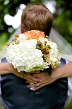 white hydrangea wedding bouquet with hypercurium berries and peach roses