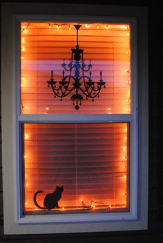 I love this Halloween window decor idea, with orange lights and black silhouettes -- it's classy and simple. (She used a chandelier decal from Target and a black cat silhouette from Martha Stewart.) lights, halloween decorations, halloween window, silhouett, orang light, halloween house, black cats, wall decals, kitchen windows