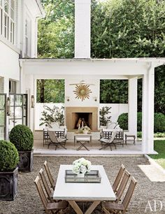 covered deck-patio with golden sunburst mirror and outdoor fireplace