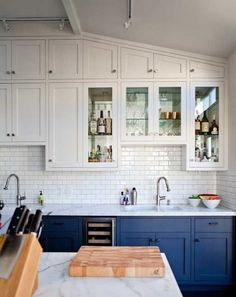 Blue lower cabinets with the white backsplash and the white upper cabinets.