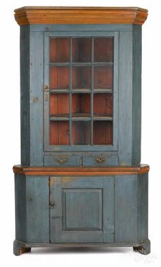 Winning bid:$3,600  Pennsylvania painted pine two-part corner cupboard, ca. 1800, retaining an old blue surface with salmon moldings, 85'' h., 47 1/2'' w.  Reduced in height. Several patches to drawers. Brasses probably original with losses. Paint enhanced.- Price Estimate: $2000 - $4000