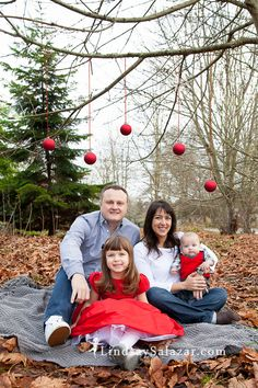 Cute and easy idea for a family Christmas card photo. Helpful tip - make sure to use a ribbon that will be visible in the photo so the ornaments don't look like they're floating. LindsaySalazar.com