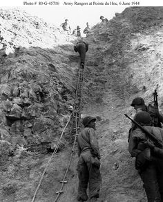 """Army Rangers show off the ladders they used to storm the cliffs at Pointe du Hoc, which they assaulted in support of """"Omaha"""" Beach landings on """"D-Day"""", 6 June 1944.Photograph was released for publication on 12 June 1944."""